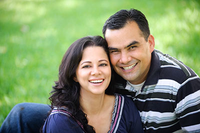 Smiling couple on the grass in Houston, TX after visiting McDonald Dental.